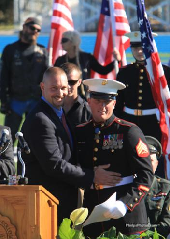 """Lindsey Wilson College Dean Chris Schmidt presented Sgt. Dakota Meyer a full four year scholarship to Lindsey Wilson College """"to be used any time in his lifetime,"""" receiving an enthusiast applause by the packed stadium."""