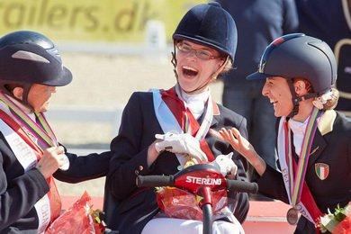 Grade 1a Freestyle gold medallist Sophie Christiansen (GBR), celebrating with compatriot Anne Dunham who took silver and bronze medallist Sara Morganti (ITA), at the JYSK FEI European Para-Dressage Championships in Herning (DEN) today. (Photo: Liz Gregg/FEI).