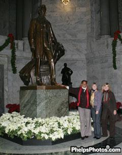 Janise Gray, Sheryl Kursar, and Mary Phelps Hathaway touch the toe of Abraham Lincoln in the Kentucky State Capitol building, a custom meant to produce good luck. In fact Lincoln's toe is well worn from all who have passed through this building.