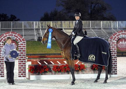 Adrienne Iverson and Huehuetenango are presented with winner's honors, including a Horze Equestrian cooler, after winning the ,000 Devoucoux Hunter Prix at HITS Ocala. ©ESI Photography