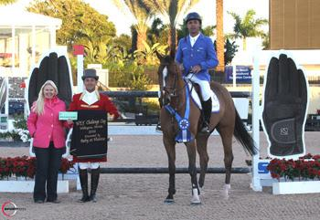 Alvaro 'Doda' Miranda, mounted on AD Uutje, is presented with a ,000 bonus from Jennifer Ward on behalf of SSG Gloves for wearing SSG 'Digitals' on his way to victory in the ,000 WEF Challenge Cup Round II at the 2014 FTI Consulting Winter Equestrian Festival in Wellington, FL. Photo by Sportfot
