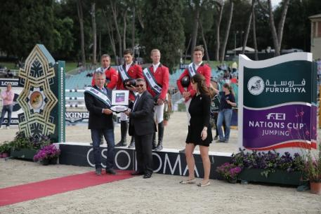 The Belgian team enjoyed their very first victory in Rome (ITA) today when winning the third leg of the Furusiyya FEI Nations Cup™ Jumping Europe Division 1 league.  Pictured on the podium are: (L to R) Ludo Philippaerts, Nicola Philippaerts, Niels Bruynseels and Constant van Paesschen.  Front (L to R) Belgian Chef d'Equipe Kurt Gravemeier, Dr Adil Nofal, Kingdom of Saudi Arabia's Deputy Ambassador to Italy and Mrs Eleonora di Giuseppe, Coordinator CSIO Rome.  Photo: Stefano Secci/FEI.