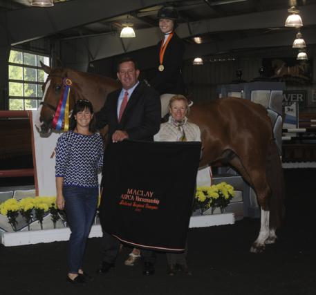 Left to Right: Brenda Tananbaum, Archie Cox and Carolyn Vincent present the top honorsto Charlotte Jacobs aboard Stallone VDL. Photo courtesy of Reflections Photography.