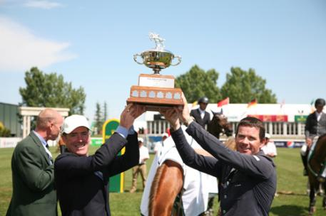 Tom Heathcott presents the Pan American Cup to grand prix winner Conor Swail. Photo © Spruce Meadows Media Services.