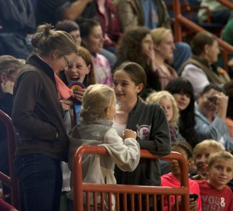 Spectators cry in excitement after catching the ribbon for Open Jumper Championship after the ribbon was tossed into the stands by winner Conor Swail on Saturday, Oct 19, 2013 at the Pennsylvania National Horse Show.