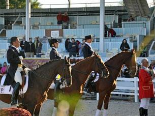 Flanked by Cesar Parra and Heather Blitz, Kassie Barteau salutes the American flag at Dressage at Devon 2010.