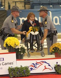 British Para rider Anne Dunham wins bronze medal grade 1V, assisted by Kentucky State Troopers to the podium