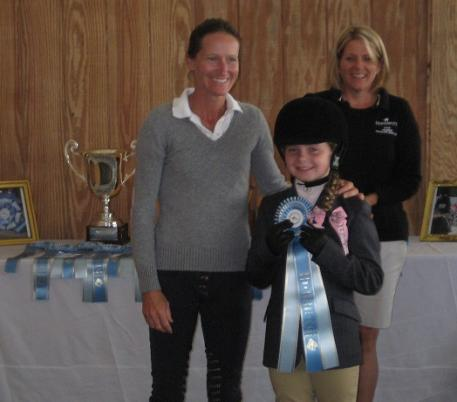 Emily McGowan (center) receives her equitation blue ribbon from grand prix rider Molly Ashe-Cawley (left) as mother Katie McGowan watches.