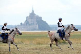 Unidentified riders with Mont St. Michel in the background.  Photo Credit: Philip Millereau