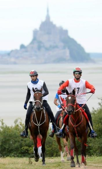 UAE team rides against a dramatic backdrop of Mont St. Michel. HH Sh Hamdam Bin Mohammed Al Maktoum (left), HE Sh Rashid Dalmook Al Maktoun (right); Raed Mahmood (rear). Photo Credit: Philip Millereau