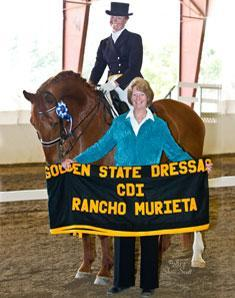 Heather Oleson and her Hanoverian mare Escorial admiring their Golden State Dressage Classic CDI cooler held by judge Jeanne Macdonald. credit: Sheri Scott