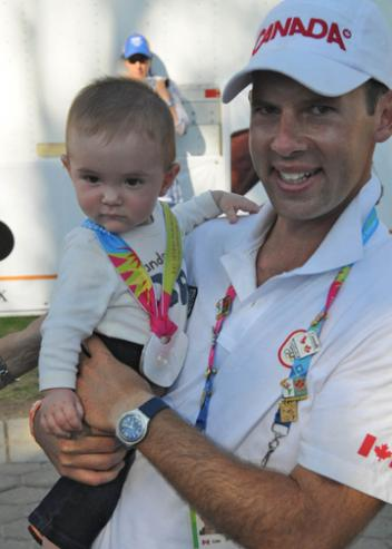 Jaimey Irwin holds Gavin, the couple's six-month-old son, as he wears his mother's Team Silver medal at the 2011 Pan American Games in Guadalajara, Mexico. (Photo: Dieter Busse)