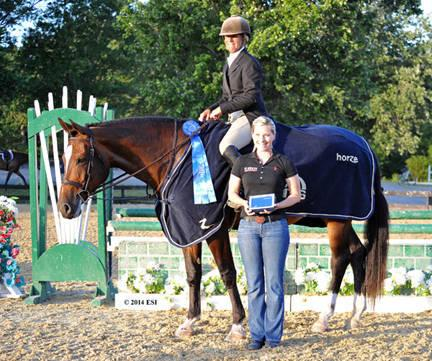 Emily Smith of Platinum Performance presents Dudley Mac Farlane and All Carolina with winner's prizes, including a Horze Equestrian cooler, after the ,500 Platinum Performance Hunter Prix at HITS Culpeper. ESI Photography