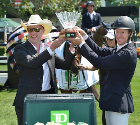 McLain Ward raises the winning trophy with Derrick Cresswell-Clough, District Vice President Alberta Central, TD Canada Trust.