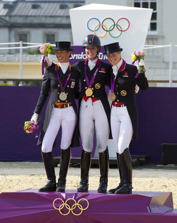 On the podium for the Dressage Freestyle which brought the equestrian events of the London 2012 Olympic Games to a close at Greenwich Park today - (L to R) - silver medallist Adelinde Cornelissen (NED), gold medallist Charlotte Dujardin (GBR), and bronze medallist Laura Bechtolsheimer (GBR).  Photo: FEI/Kit Houghton.