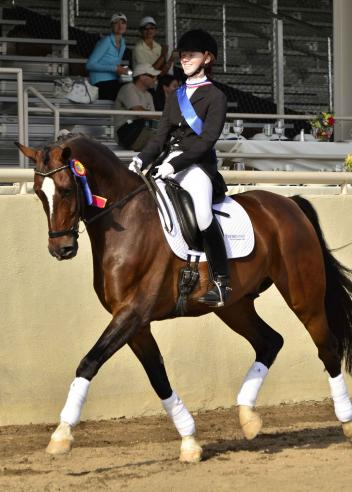 Gold Medalist Mickayla Frederick shows off her championship ribbons and HorseShow.com saddle pad during her victory lap at the 2013 USEF Dressage Seat Medal Finals. (Photo: yourhorses.ifp3.com/Kathleen Bryan)