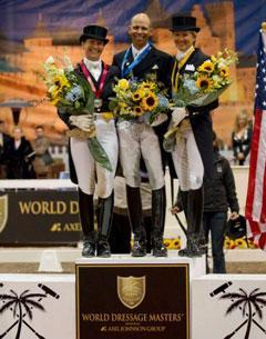 Tinne Vilhelmsson Silfven, Steffen Peters and Tina Konyot stand on the podium before a back drop of a Southern French scene during the awards presentation. (Photo Credit: Susan J. Stickle for Phelps Media Group)