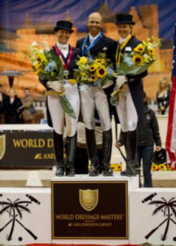 Tinne Vilhelmsson Silfven, Steffen Peters and Tina Konyot stand on the podium before a back drop of a Southern French scene during the awards presentation. (Photo By: Susan J. Stickle)