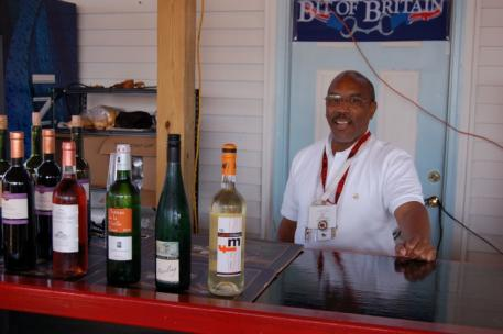 Ron Blair greeter, wine pourer, smiling face, and factotum at the beer and wine kiosk on the Devon midway. (Photo: Ruth McCormick)