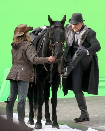 Cari Swanson helps Russell Crowe mount during the filming of A Winter's Tale in New York City.