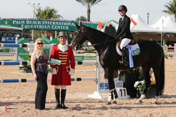 "Sarah Hubbard riding Athina Z is presented with a ,000 bonus from SSG Gloves ""Go Clean for the Green"" promotion manager Jennifer Ward and ringmaster Gustavo Murcia for wearing SSG 'Digitals' on her way to victory in the ,000 High Amateur-Owner Classic held February 8 at the 2014 FTI Consulting Winter Equestrian Festival in Wellington, FL. Photo by Sportfot"