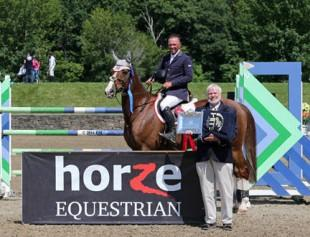 Tony Hitchcock of HITS present top honors, including a Horze Equestrian cooler, to Todd Minikus and Arino Du Rouet after the $50,000 Horze Equestrian Grand Prix presented by Zoetis at HITS Saugerties. ©ESI Photography