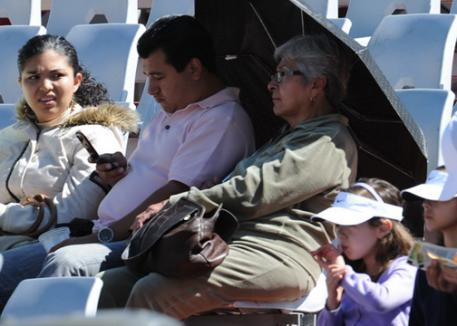 Spectators cuddled up under umbrellas to protect themselves from the sun.(photo: Diana de Rosa)