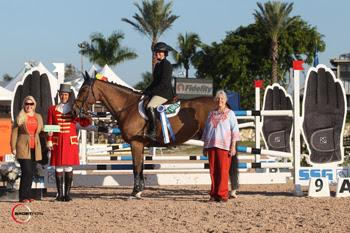 "Victoria Colvin, mounted on Don Juan, is presented with a $1,000 bonus from SSG Gloves ""Go Clean for the Green"" promotion manager Jennifer Ward (far left) following her victory in the $10,000 High Junior Jumper Classic at the 2014 FTI Consulting Winter Equestrian Festival in Wellington, FL. Photo by Sportfot"