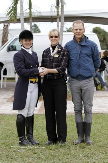 Alex Dvorak is congratulated by IHS Palm Beach Dressage Derby show manager Noreen O'Sullivan and Dad Tom Dvorak for winning the Courtney King Dye Helmet Awareness Award. Sponsored by Hampton Green Farm, Renee Isler and GPA Helmet, the highest scoring rider wearing a helmet in the CDI Young Riders.