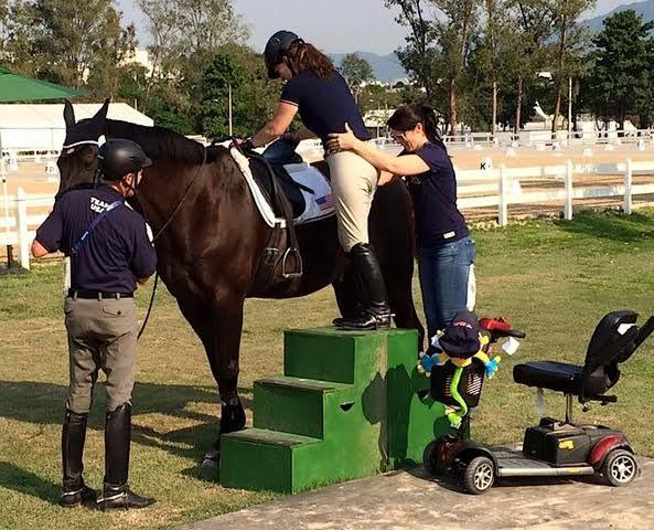 Grade 1A rider Roxanne Trunnell getting assistance to mount NTEC Royal Dancer.