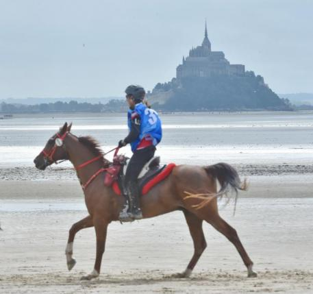 Jessica Manness and Greater Glide loping down the beach across from Bay of Mont Saint Michel. Photo by Diana DeRosa