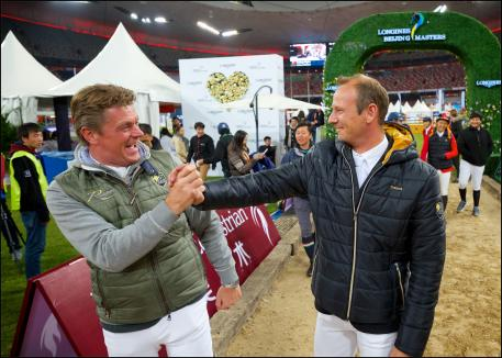 Jeroen Dubbeldam congratulates Marco Kutscher for his victory in the team jumping competition.
