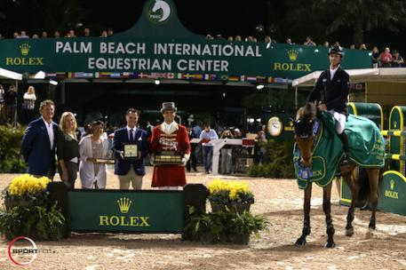 Ben Maher and Sarena in their winning presentation with Equestrian Sport Productions CEO Mark Bellissimo; Wellington Equestrian Partners Principal  Katherine Bellissimo; Wellington Equestrian Partners' Marsha Dammerman;  Joël Aeschlimann, Head of Sponsorship, Rolex; and ringmaster Christian Craig.