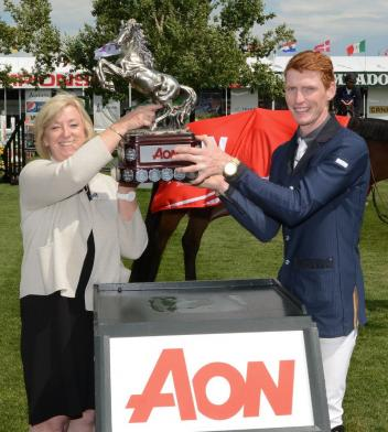 Daniel Coyle lifts the winning trophy with Christine Lithgow, President & CEO, AON.