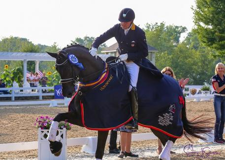 Endel Ots gives Lucky Strike a pat while leading the victory lap for their US/Markel USEF Developing Prix St. George win. ©SusabJStickle.com