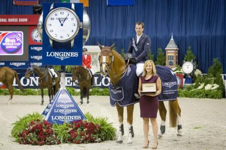 Harrie Smolders (NED) and Emerald (left), winners of the Longines FEI World Cup™ Jumping at the Washington International Horse Show, were presented with a Longines watch by Taylor Mace, National Event Manager for Longines.