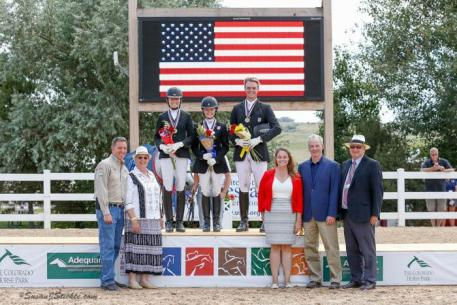 Jenna Upchurch, Vanessa Creech-Terauds, and Jackson Gillespie in their medal ceremony for the USDF North American Junior & Young Rider Dressage Championships Junior Rider Freestyle with Allyn Mann of Adequan®; Jennie Loriston Clarke, Foreign Technical Delegate; Hannah Niebielski, USEF Director of Dressage National Programs; Stephan Hienzsch, Executive Director of USDF; and Michael Stone, President of The Colorado Horse Park.
