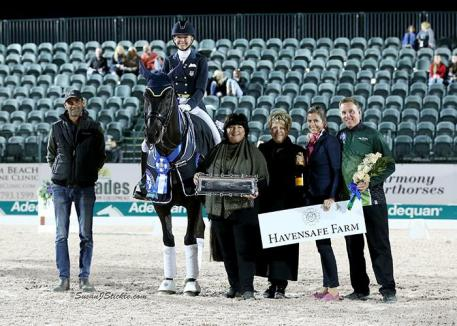 Katherine Bateson-Chandler and Alcazar in their presentation ceremony with groom Carl Chandler, Elizabeth Juliano of Havensafe Farm, judge Janet Foy (USA), Cora Causemann of AGDF, and Allyn Mann of Adequan®.