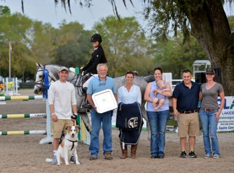 Logan Taylor and Secretive winning the $25,000 Marshall & Sterling / Team Barber Child-Adult Jumper Classic pictured with Dr. Robert Barber.