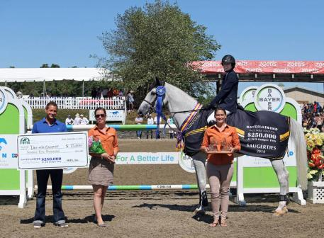 Sean Niland of Bayer is joined by HITS representatives Asia Manning and Lindsay Yandon to present top honors, including a Horseware Ireland cooler and $75,000 winner's check, to Danielle Cooper and Calantus. ©ESI Photography