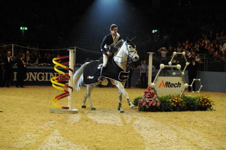 David Simpson circles the Olympia arena on his mare Richi Rich after winning the Alltech Christmas Puissance at Olympia, London. Credit: Kit Houghton.