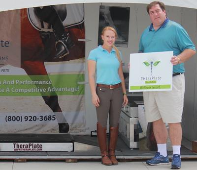 Chip Kreiling (right) of TheraPlate Revolution presents Mary Rollins (left) with the TheraPlate Award at TheraPlate's booth at the Adequan Global Dressage Festival