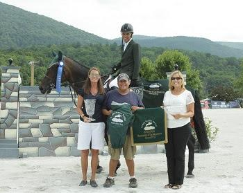 Jimmy Torano, mounted on Wannahave, celebrates his win in the $30,000 Manchester & the Mountains Grand Prix, with, from left to right, Vermont Summer Festival Awards Coordinator Jennifer Glass, groom Gerardo Briseño, and Vermont Summer Festival Marketing Director Ruth Lacey. Photo by David Mullinix Photography
