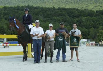 Julie Welles, mounted on Twan, is presented as the winner of the $50,000 Vermont Summer Celebration Grand Prix at the Vermont Summer Festival.  From left to right, John Brennan, Missy Clark, Ulises Gonzalez, and Jonathan Cohen hold Danny and Ron's Rescue Ambassadors Dandelion Clark, Chili Dog and Louis.  Photo by David Mullinix Photography