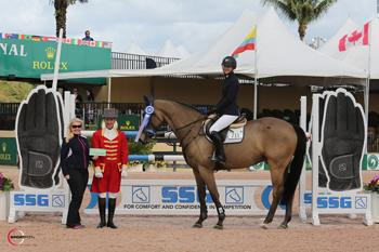Kaely Tomeu, riding Fidalgo van het Leliehof, is presented with a ,000 bonus from Jennifer Ward on behalf of SSG Gloves for wearing SSG 'Digitals' on her way to victory in the 5,000 High Amateur-Owner Jumper Classic at the Winter Equestrian Festival in Wellington, FL. Photo by Sportfot