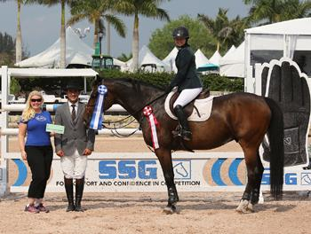 "Daisy Farish, 14, won her first 0,000 High Junior Jumper Classic during week 11 of the Winter Equestrian Festival.  For wearing SSG 'Digital' riding gloves on her way to victory, Farish was presented with a ,000 bonus from Jennifer Ward, accompanied by Gustavo Murcia, in the SSG Gloves ""Go Clean for the Green"" promotion. Photo by Sportfot"