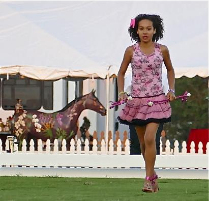 Baton twirler Kayden Muller led the procession to the piping tunes of Shirley Temple Black, the pink motif customary at the 2015 Challenge of the Americas.