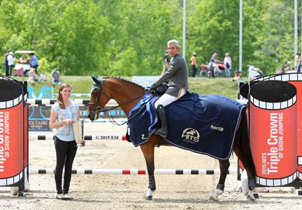 Ronan McGuigan and his Capall Zidane are presented with the blue ribbon after winning the $50,000 HITS Grand Prix on Sunday, May 24, 2015. (c) ESI Photography
