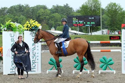 Sarah Segal and Chartwell's Ubris are presented with a Horseware Ireland cooler and the blue ribbon after winning the $75,000 Horseware Ireland Grand Prix at HITS-on-the-Hudson II (Photo: ESI Photography)