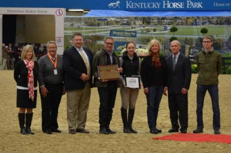 USHJA's Maria Holt, Zone 5 Chairpersons Diane Carney and Patrick Boyle, Greg Darst, Maddy Darst, Patti Rogers, USHJA President Bill Maroney and John Darst for the presentation of the Posthumous Award to the late Mindy Darst. Photo by Chicago Equestrian.